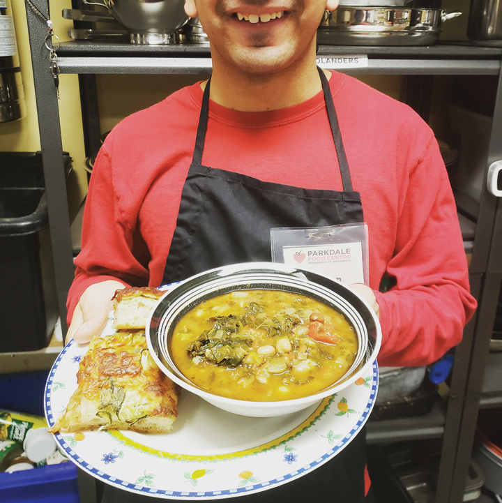 A volunteer holds a soup bowl and plate with bread on it at the Parkdale Food Centre