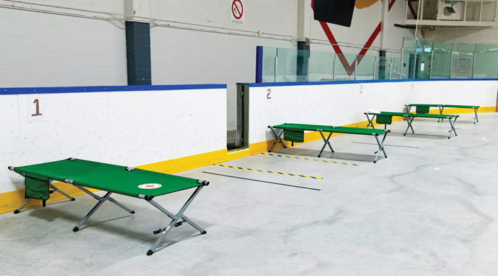 Green cots are set up six feet apart on the floor of the Tom Brown Arena Respite Centre