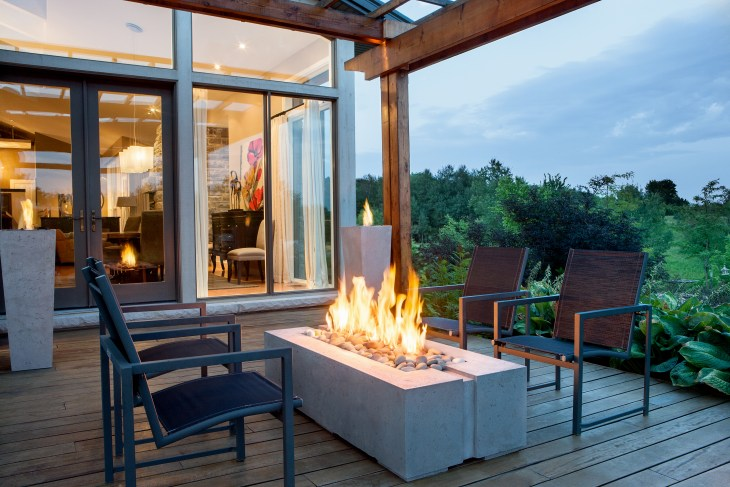 A outdoor fireplace is seen at night with four black chairs around it