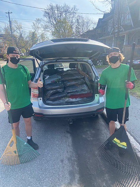 Two teens stand with rakes next to an open trunk of a vehicle with bags of manure and mulch in it