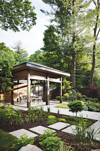 A gazebo is seen in a backyard surrounded by trees and plants in a lawn