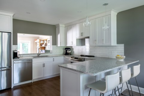A renovated kitchen in a Westboro home is seen. It has a dark wood floor and white kitchen cabinets and chairs.