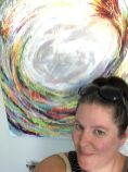 A headshot of Pamela Stewart in front of a multicoloured circle on a painting