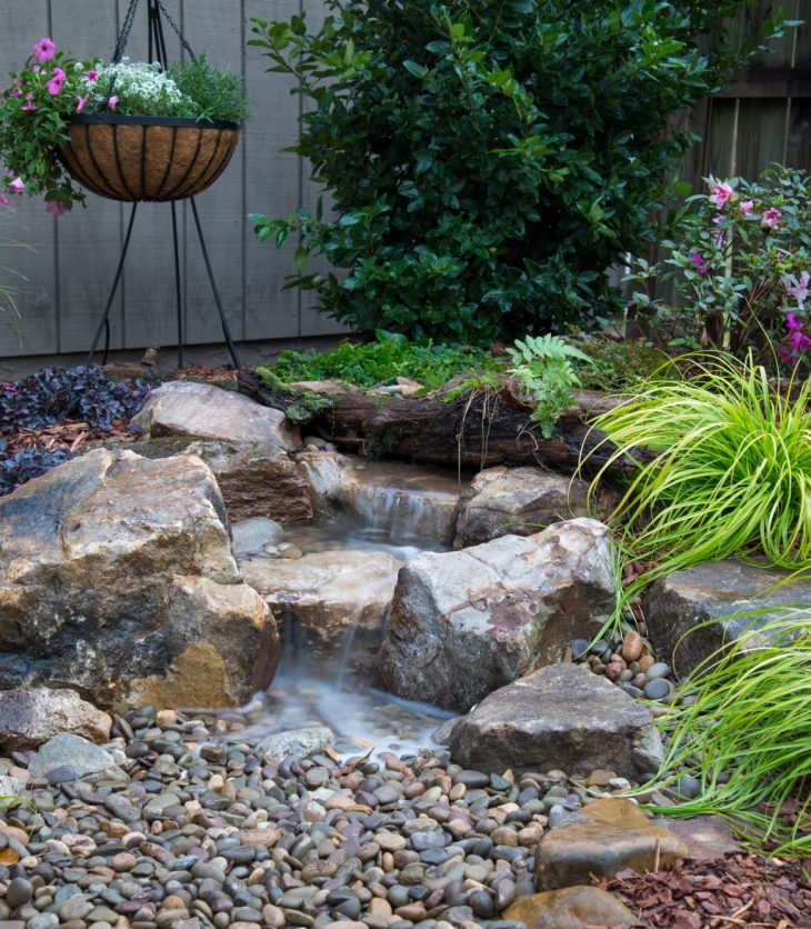 A small waterfalll is seen in a rockgarden in a home backyard in Ottawa