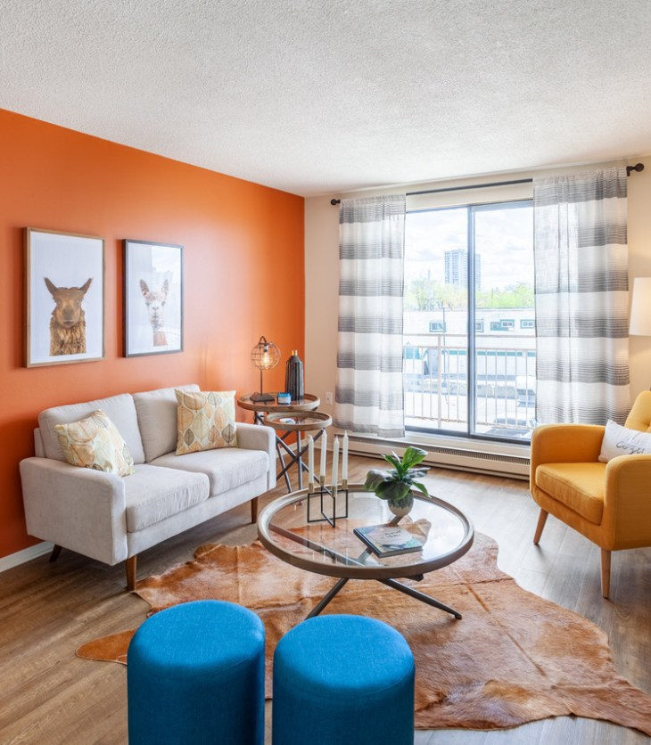A living room with a white couch, yellow chair, blue ottomans and an orange wall is seen with a large set of windows