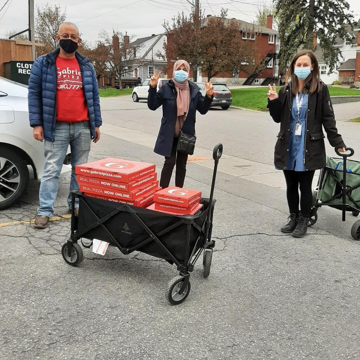 There people stand next to a black wagon carrying 15 red pizza boxes from Gabriel's Pizza on an overcast day in Ottawa