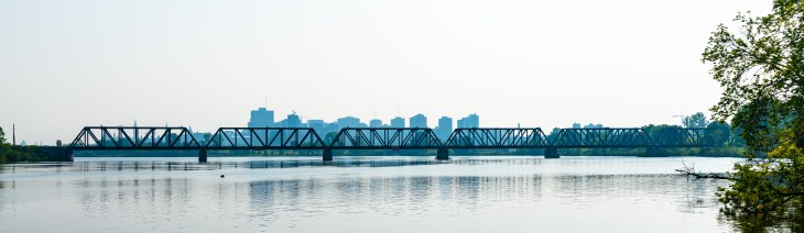 A bridge is seen from the distance across the Ottawa River on a summer day in Ottawa. The sky is smoky and buildings are seen in the distance.