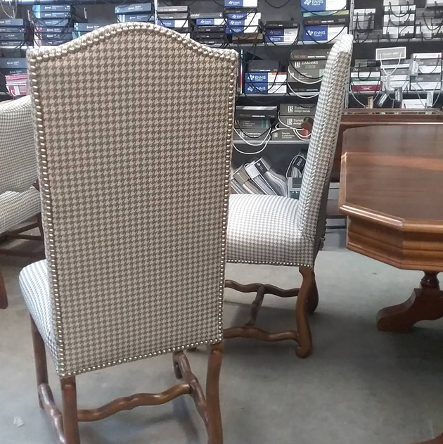 A white and black pattern chair sits in front of two others like it in a furniture store