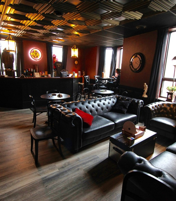 A dark Escape Manor lounge with red walls and black leather furniture with the lights turned down low