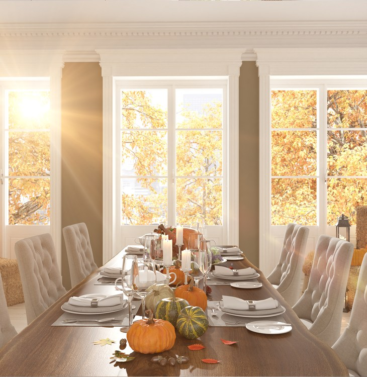 A living room table with pumpkins on it and light streaming through the window