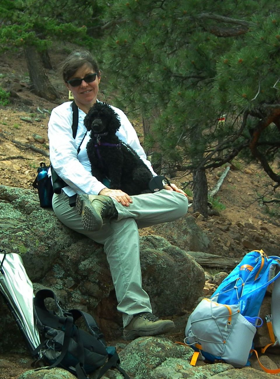 Female hiker and miniature poodle taking a break. Photo by Kurt Fristrup