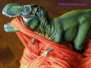 Tiny the T-rex, playing with the yarn I bought for her sweater.