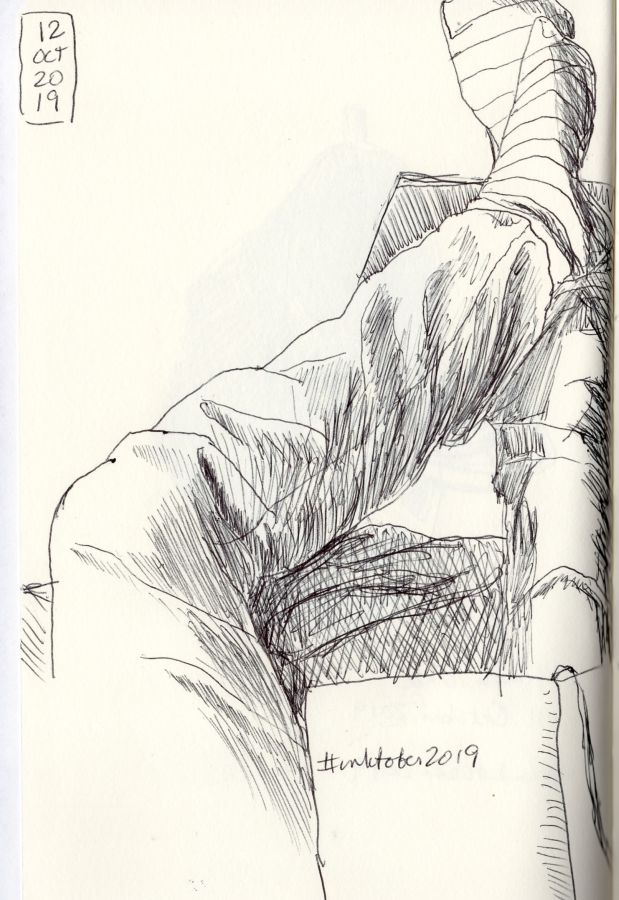 Ink drawing of crossed legs in jeans. Drawing by Kit Dunsmore
