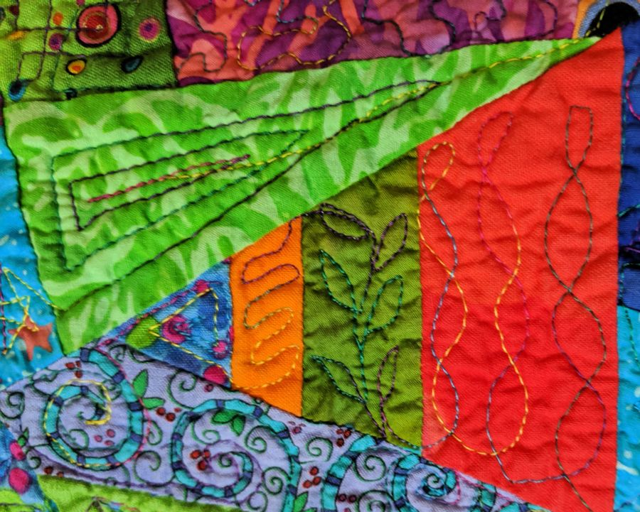 Close up of quilt; irregular triangles in bright colors with free-motion stitching. Quilt by Kit Dunsmore