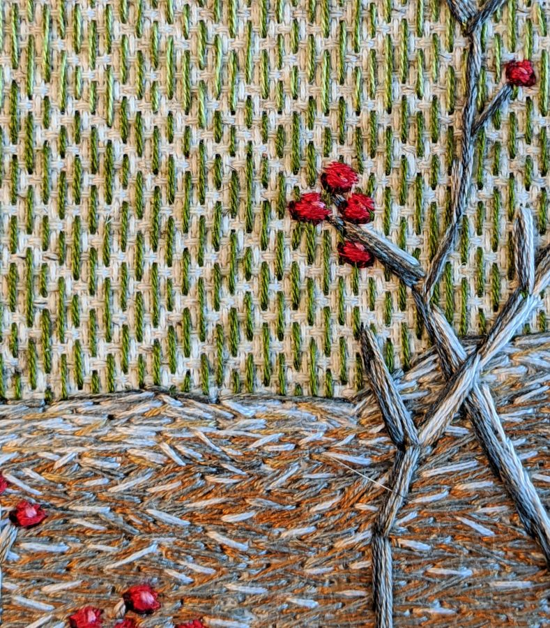 Close up of embroidered log, twigs and berries with green straight stitch background by Kit Dunsmore.