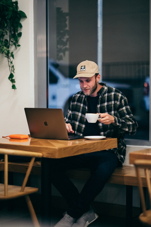 man drinking coffee while working on laptop