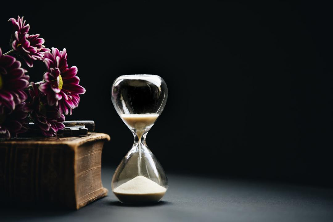image of clear hour glass beside pink flowers