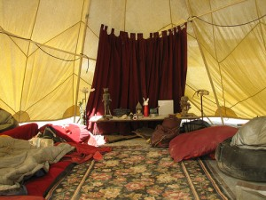 A shady dome with blankets and cushions as well as a beautiful altar.