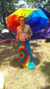 Kit is dressed in a rainbow sarong, rainbow face bandanna, and holding a rainbow umbrella while standing outside the Purple Taco.