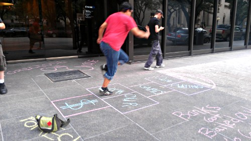 An occupier plays hopscotch on a chalk covered sidewalk.