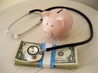 A piggy bank and stethoscope listening to a stack of money