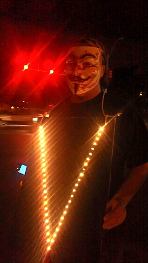 Anonymous holds a lighted 'V' sign
