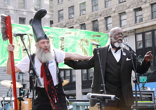 Vermin Supreme (with a boot on his head & toothbrush) with a friend in a suit