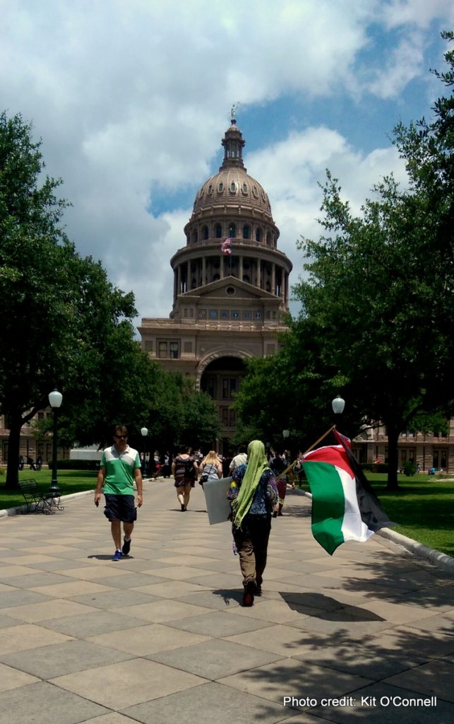 A woman in a bright green hijab and carrying a Palestinian flag walks up to the Texas Capitol for a Palestine rally on Aug. 4, 2014. (Kit O'Connell)