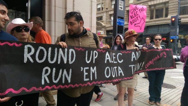 "At a July 31, 2014 CODEPINK Rally outside Neiman Marcus in Dallas, Texas, activists hold a banner reading ""Round Up ALEC and Run 'Em Outa Town."" (Kit O'Connell)"