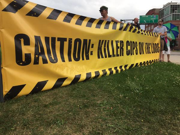 "Activists protest the killing of Paul Castaway in Denver, Colorado on June, 20 2015. A banner reads ""Caution: Killer Cops."" (Twitter / Jesse Benn)"