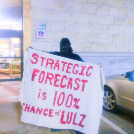 """An """"Anonymous gorilla"""" (a protester in a gorilla suit) stood outside Book People in Austin, Texas on February 2, 2015 during George Friedman's book signing. The gorilla's banner reads """"Strategic Forecast Is 100% Chance Of Lulz."""" (Kit O'Connell)"""