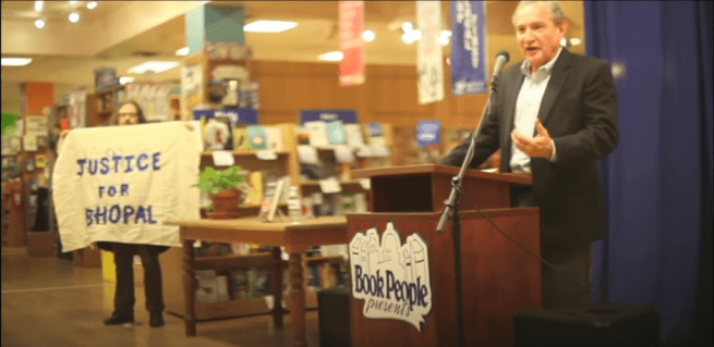 "In this Feb 2. 2015 photograph, George Friedman, CEO of Strategic Forecasting, speaks at a podium while Kit O'Connell stands nearby with a banner reading ""Justice for Bhopal,"" at BookPeople in Austin, Texas. (YouTube screenshot)"