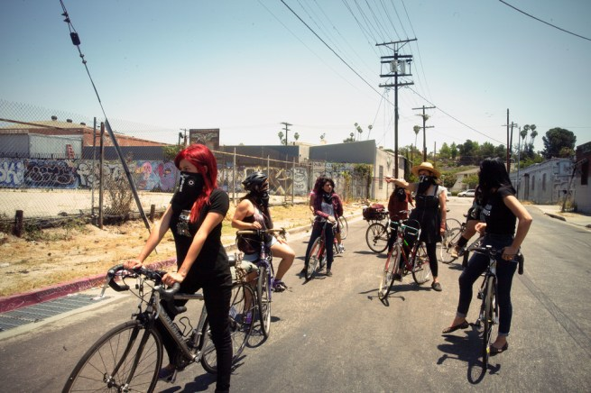 A photo of the Ovarian Psycos, a group of women of color cyclists in East Los Angeles, on their bicycles on an urban street. (Ovarian Psycos publicity still)