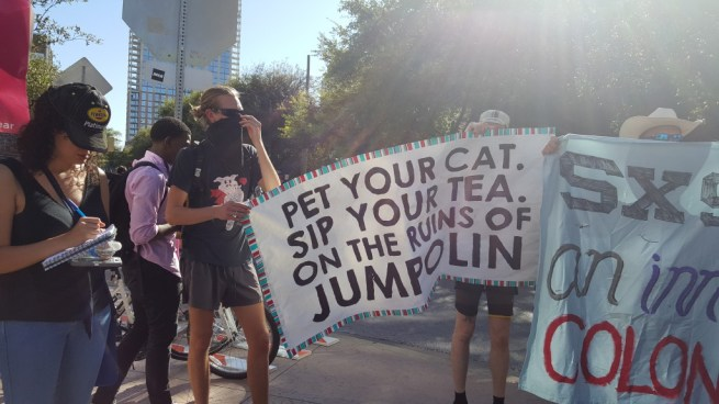 "In this March 13, 2016 photograph, activists hold a banner reading ""Pet Your Cat, Sip Your Tea, On The Ruins Of Jumpolin."" (Kit O'Connell)"