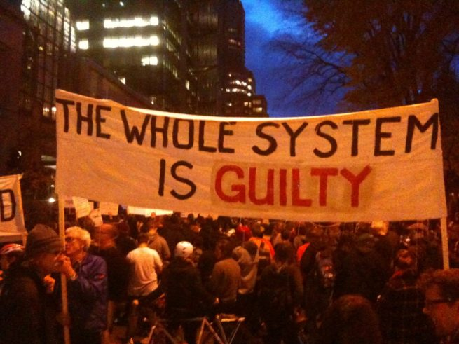 """In this Nov. 25, 2014 photograph, activists in Portland, Oregon march for Ferguson with a banner reading """"The Whole System Is Guilty."""" (Flickr / Sarah Mirk)"""