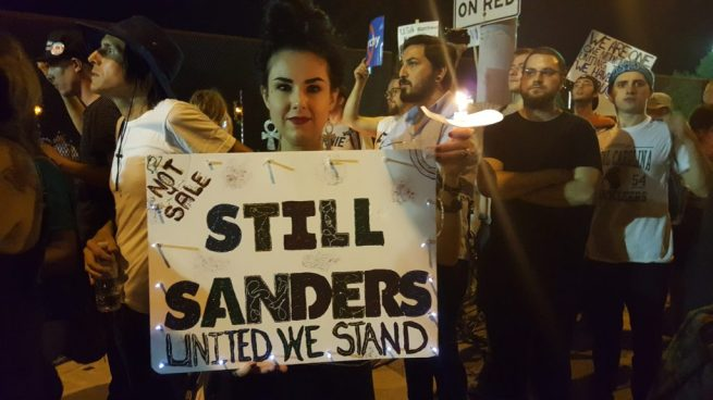 """An activist holds a """"Still Sanders"""" sign during a candlelit vigil outside the Wells Fargo Center in Philadelphia, site of the 2016 Democratic National Convention, July 27, 2016. (Kit O'Connell)"""