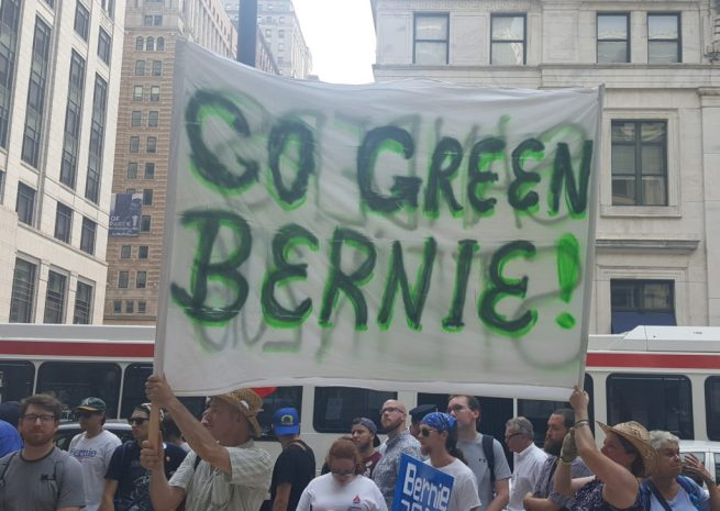 """In this July 25, 2016 photograph, activists hold a """"Go Green Bernie"""" banner at Philadelphia City Hall during the """"March For Our Lives"""" rally. (Kit O'Connell)"""