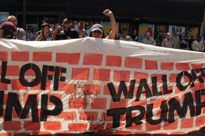 """July 19, 2016. An activist holds up a fist behind a """"Wall Off Trump"""" banner, painted with a brick wall pattern and inscried """"No human being is illegal."""" RNC 2016. (MintPress News / Desiree Kane)"""