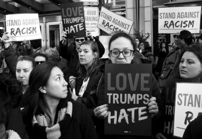 "Protesters hold signs reading ""Love Trumps Hate"" and ""Stand Against Racism"" during Donald Trump's speech to AIPAC. March 21, 2016. (Flickr / Stephen Melkisethian)"
