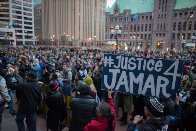 Protesters rally with a #Justice4Jamar sign in Minneapolis, Minnesota after the county attorney declined to charge the police that killed Jamar Clark. March 30, 2015. (Flickr / Fibonacci Blue)