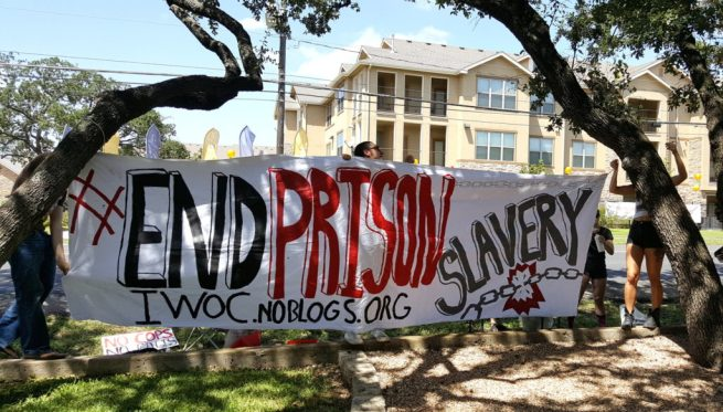 """Activists hold a banner that reads """"End Prison Slavery"""" while protesting at Texas Correctional Industries' showroom in south Austin, Texas in solidarity with the National Prison Strike. September 9, 2016. (Kit O'Connell)"""