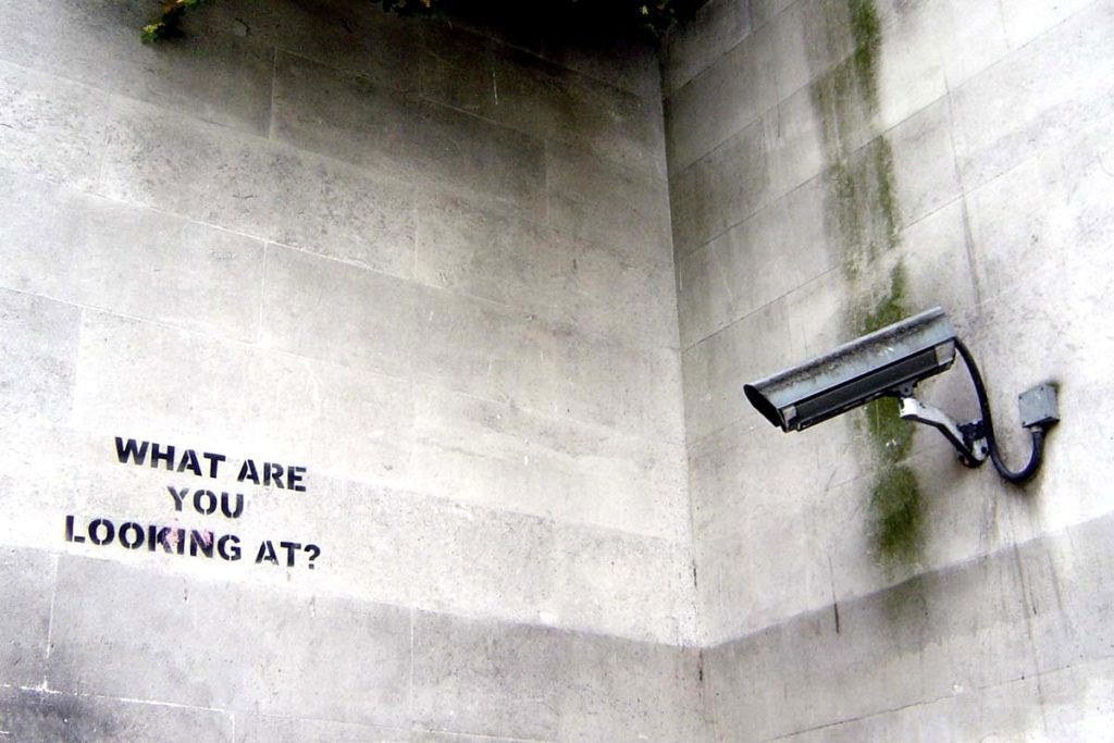 """A stencil by Banksy on a wall opposite a surveillance camera reads, """"What are you looking at?"""" (Flickr / nolifebeforecoffee)"""