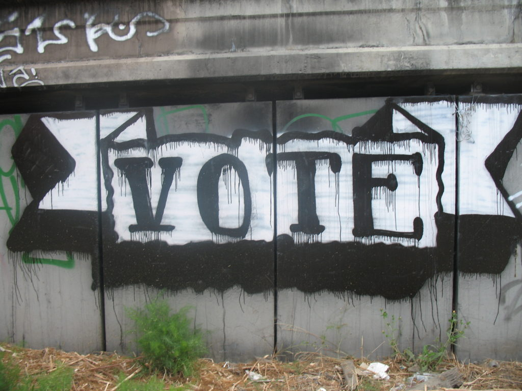"""Graffiti on a fence reads """"VOTE."""" (Flickr / H2Woah!)"""