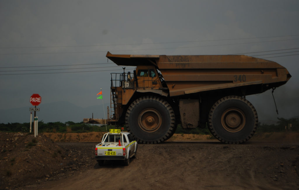 A massive coal mining vehicle towers over a pickup truck at the intersection of a desolate mining road. El Cerrejón, Guajira, Colombia, June 5 2009. (Flickr / Santiago La Rotta)