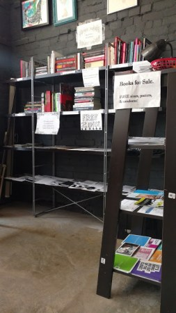 Black Rose Book Distro bookshelves with books, zines, and safer sex supplies