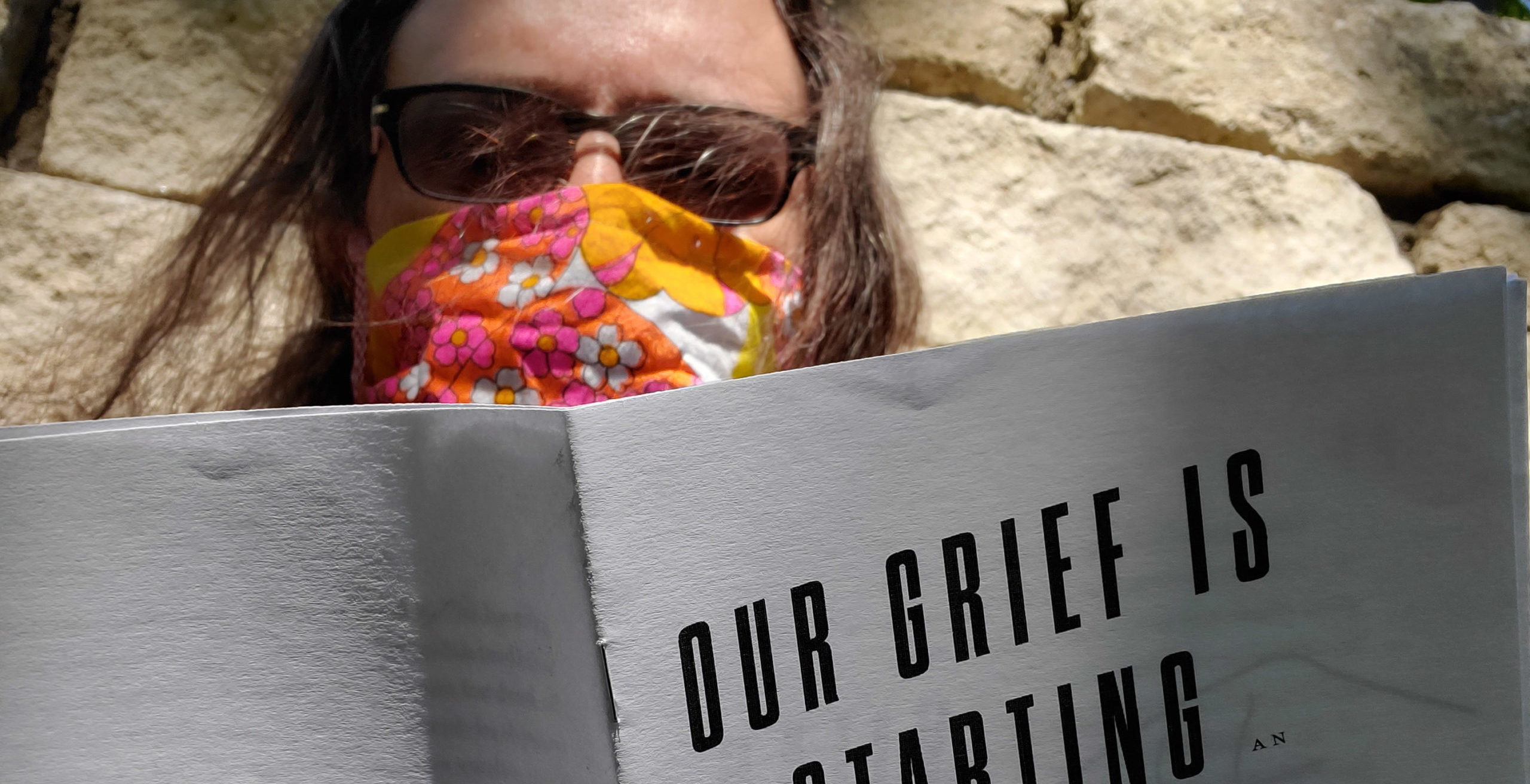 "A portrait of Kit posed against a stone wall, his brown hair blowing in his face as he reads ""Our Grief Is A Starting Point In The Fight Against Fascism,"" a zine by Cindy Milstein (part of the Virtual Gonzo Zine Library Spring Edition). He's wearing sunglasses and a colorful 70s flower print face mask covering his mouth and nose."