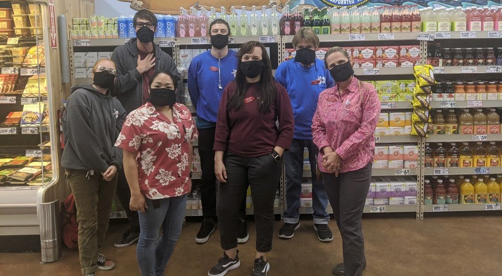 Workers at a Trader Joe's pose in hemp masks created and donated by iLoveBad and The Hemp Cooperative.