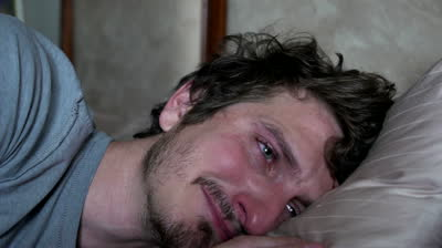 stock-footage-man-crying-laying-on-pillow-in-bed