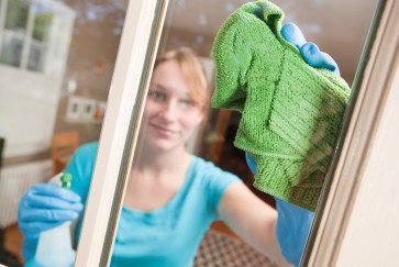 Young Woman Cleaning Window with Towel and Spray Detergent Product