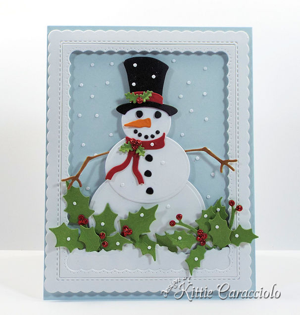 Come see how I made this fun die cut snowman scene with falling snow and holly.